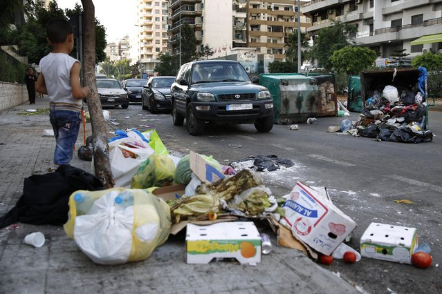 A Syrian boy watches vehicles driving past dumpsters and a pile of garbage in Beirut, Lebanon, Sunday, July 26, 2015. (Photo by Hassan Ammar/AP Photo)
