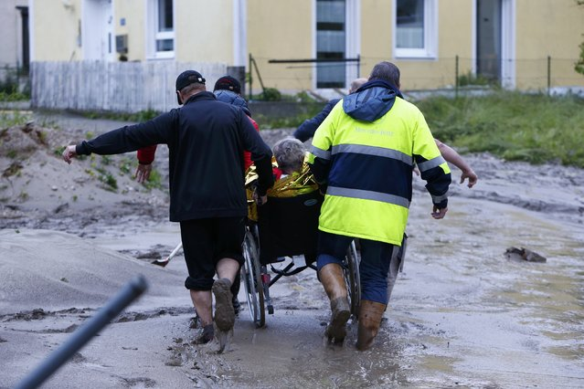 People carry an elderly woman on a wheelchair over mud covered street after floods in the Bavarian village of Simbach am Inn east of Munich, Germany, June 1, 2016. (Photo by Michaela Rehle/Reuters)