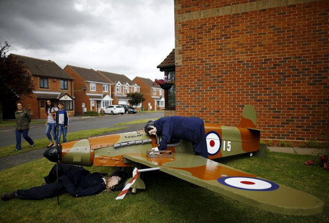 Visitors look at a scarecrow of mechanics working on a Spitfire airplane during the Scarecrow Festival in Heather, Britain, July 28, 2015. (Photo by Darren Staples/Reuters)