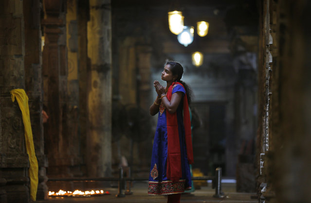 In this June 3, 2016, photo, a Sri Lankan ethnic Tamil woman prays at a Hindu temple in Colombo, Sri Lanka, Friday, June 3, 2016. For the hundreds of thousands of minority ethnic Tamils, the Sri Lankan government's repeated promises of post-war reconciliation ring false, even as authorities take tentative steps toward fulfilling some of them. Many expected a new era of healing and atonement when President Maithripala Sirisena took office in 2015, but progress has been slow as he cautiously balances the Tamils' anguished demands with the persistent fears of the Sinhalese majority. (Photo by Eranga Jayawardena/AP Photo)