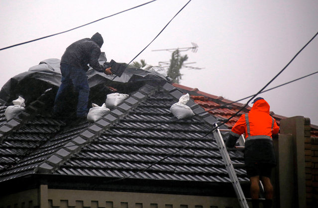 Two men work on covering a damaged roof on a house in severe weather bringing strong winds and heavy rain hits the eastern coast of Australia near Coogee Beach in Sydney, June 5, 2016. (Photo by David Gray/Reuters)