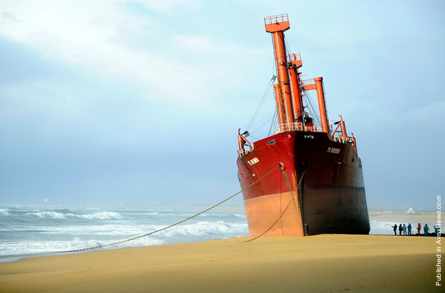 Rescue workers stand next to TK Bremen cargo ship which ran aground during a powerful storm, spilling oil off the coast of France's northwestern region of Brittany as it lies stranded on Kerminihy beach in Erdeven, on December 16, 2011