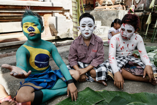 Young members of the village community gather at Duur Bingin temple before walking around their village with painted bodies during the Grebeg Ritual on June 25, 2014 in Tegallalang Village, Gianyar, Bali, Indonesia. During the biannual ritual, young members of the community parade through the village with painted faces and bodies to ward off evil spirits. (Photo by Putu Sayoga/Getty Images)