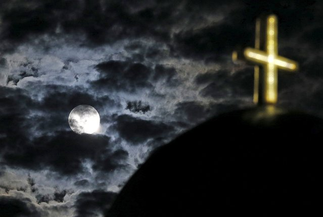 The moon rises above a church on the Greek island of Santorini, Greece, July 1, 2015. (Photo by Cathal McNaughton/Reuters)