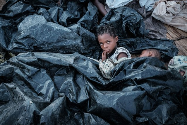 Enia Joaquin Luis, 11, wakes up beside her sister Luisa, 6, under plastic sheets for protect themselves from rain as they stay in shelter at the stands of Ring ground in Buzi, Mozambique, on March 23, 2019. The death toll in Mozambique on March 23, 2019 climbed to 417 after a cyclone pummelled swathes of the southern African country, flooding thousands of square kilometres, as the UN stepped up calls for more help for survivors. Cyclone Idai smashed into the coast of central Mozambique last week, unleashing hurricane-force winds and rains that flooded the hinterland and drenched eastern Zimbabwe leaving a trail of destruction. (Photo by Yasuyoshi Chiba/AFP Photo)