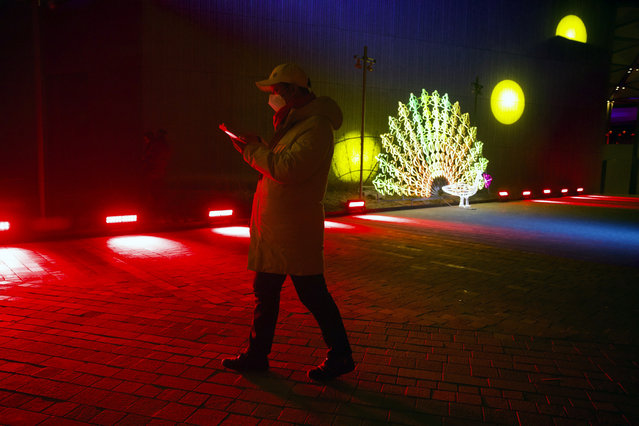 A man walks near a light sculpture before a New Year's Eve countdown event at the 2022 Beijing Winter Olympic headquarters in Bejiing, Tuesday, December 31, 2019. Revelers around the globe are bidding farewell to a decade that will be remembered for the rise of social media, the Arab Spring, the #MeToo movement and, of course, President Donald Trump. (Photo by Ng Han Guan/AP Photo)