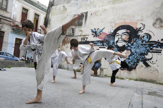 """Children practice martial arts near a graffiti of Revolutionary hero Ernesto """"Che"""" Guevara in Havana February 6, 2015. (Photo by Enrique De La Osa/Reuters)"""