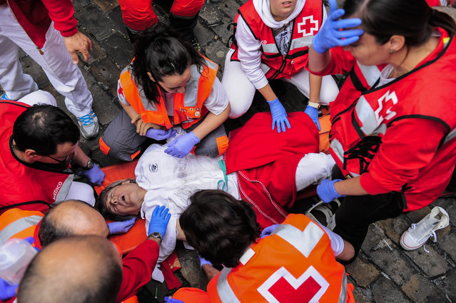 """Medical assistants help a participant injured during the running of the bulls with """"Torrestrella"""" fighting bulls, at the San Fermin festival, in Pamplona, Spain, Monday, July 7, 2014. (Photo by Alvaro Barrientos/AP Photo)"""