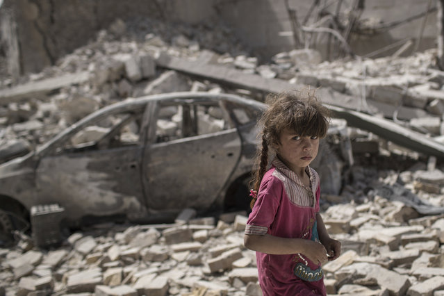 An Iraqi girl flees through a destroyed street as Iraqi Special Forces continue their advance against Islamic State militants in the Old City of Mosul, Iraq, Sunday, July 2, 2017. (Photo by Felipe Dana/AP Photo)