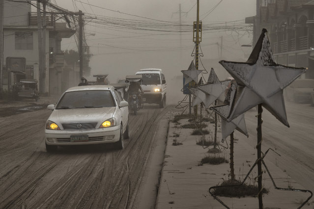 Motorists drive through a road covered in volcanic ash from Taal Volcano's eruption on January 13, 2020 in Lemery, Batangas province, Philippines. (Photo by Ezra Acayan/Getty Images)