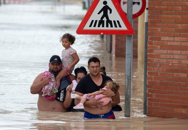 Peolple carry children on a flooded street in Almoradi on September 13, 2019. Two more people died as torrential rain and flash floods battered southeastern Spain, raising the death toll to four as the storm caused havoc for travellers and forced 3,500 people from their homes. (Photo by Jose Jordan/AFP Photo)