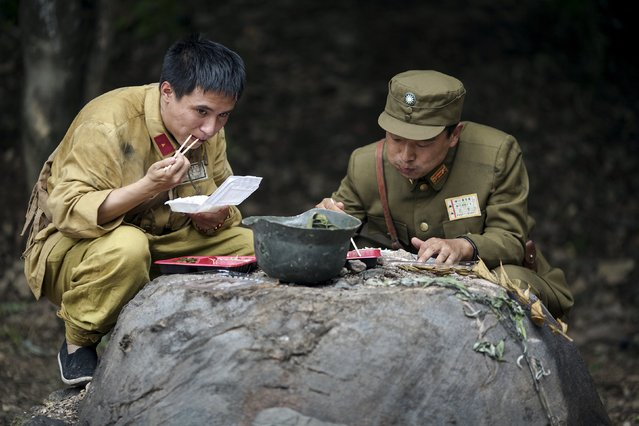 """Actors dressed as Chinese World War Two soldiers eat their lunch on the set of """"The Last Prince"""" television series on location near Hengdian World Studios near Hengdian July 24, 2015. (Photo by Damir Sagolj/Reuters)"""