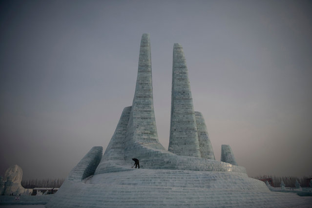 A worker clears some snow before tourists arrive at the Harbin International Ice and Snow Festival in Harbin, in China's northeast Heilongjiang province on January 6, 2020. China's annual ice festival in Harbin has kicked off late on January 5 with couples lining up for a snow-themed mass wedding, swimmers braving frigid waters and frozen palaces rising from the ground. (Photo by Noel Celis/AFP Photo)