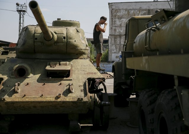A worker stands at old soviet tank T-34 as he fixes military vehicle (R) at Phaeton museum in Zaporizhia, Ukraine, August 11, 2015. (Photo by Gleb Garanich/Reuters)