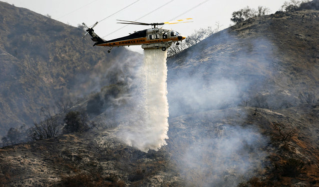 A Los Angeles County firefighting helicopter makes a water drop on a hill near a wildfire in Duarte, Calif. Tuesday, June 21, 2016. Firefighters worked to make gains against Southern California wildfires as an intense heat wave eased slightly Tuesday, but officials warned nearby communities to stay alert and obey any evacuation orders. (Photo by Nick Ut/AP Photo)