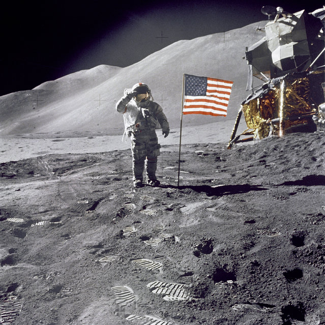 "Astronaut David R. Scott, commander, gives a military salute while standing beside the deployed U.S. flag during the Apollo 15 lunar surface extravehicular activity (EVA) at the Hadley-Apennine landing site. The flag was deployed toward the end of EVA-2. The Lunar Module ""Falcon"" is partially visible on the right. Hadley Delta in the background rises approximately 4,000 meters (about 13,124 feet) above the plain. The base of the mountain is approximately 5 kilometers (about 3 statute miles) away. (Photo by NASA)"