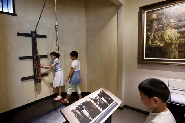 Children look at a sculpture of a gallow during a media trip at the Shanghai Songhu Campaign Memorial Hall in Shanghai, August 13, 2015. (Photo by Aly Song/Reuters)