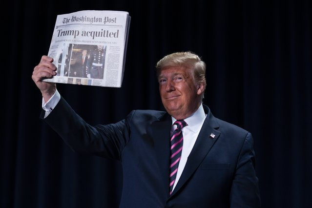 """President Donald Trump holds up a newspaper with the headline that reads """"Trump acquitted"""" during the 68th annual National Prayer Breakfast, at the Washington Hilton, Thursday, February 6, 2020, in Washington. (Photo by Evan Vucci/AP Photo)"""