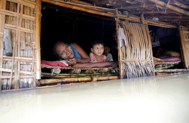 A elderly woman and a child look out of a half-flooded house at Kan Gyee Daunt township of Ayeyarwaddy Region, Myanmar, 13 August 2015. Myanmar's government warned low-lying regions to expect even more flooding after heavy rainfall brought havoc to higher areas further north. (Photo by Lynn Bo Bo/EPA)