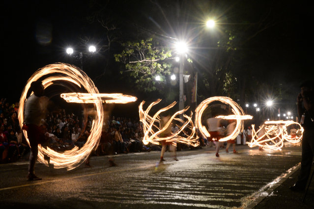 "In this photograph taken on August 14, 2019 fire-dancers perform during the ""Esala Perahera"" festival near the Buddhist temple of the Tooth in the ancient hill capital of Kandy, some 116 kilometres from Colombo. The Temple of the Tooth, Buddhism's holiest shrine on the island, holds the annual festival with traditional drummers and dancers as well as nearly 100 tamed elephants. (Photo by Lakruwan Wanniarachchi/AFP Photo)"