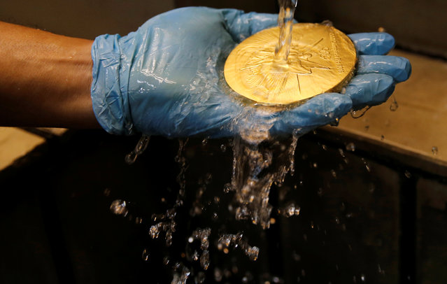 A worker from the Casa da Moeda do Brasil (Brazilian Mint) holds a Rio 2016 Olympic medal in an acid bath in Rio de Janeiro, Brazil, June 28, 2016. (Photo by Sergio Moraes/Reuters)
