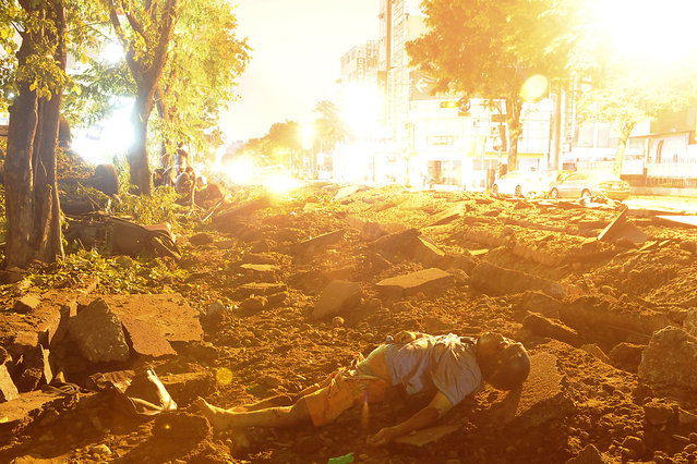A person is seen lying on the ground after an explosion in Kaohsiung, southern Taiwan, August 1, 2014. An explosion caused by a gas leak in the southern Taiwanese city Kaohsiung has killed 15 people and injured another 243, Taiwanese media reported on Friday. (Photo by Reuters/Stringer)