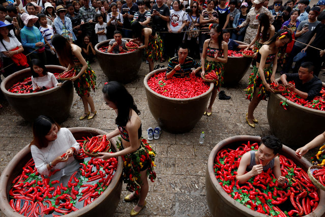Participants sit in vats with hot peppers as they compete eating them in Lijiang, Yunnan Province, China, July 2, 2016. (Photo by Reuters/Stringer)