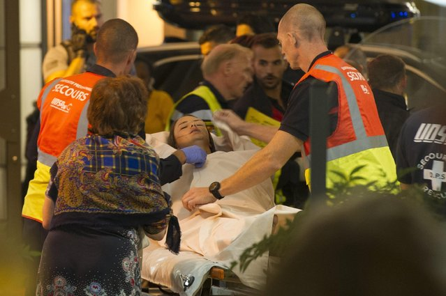 Emergency team assist wounded people as they evacuate from the scene where a truck crashed into the crowd during the Bastille Day celebrations in Nice, France, 14 July 2016. According to reports, at least 70 people died and many were wounded after a truck drove into the crowd on the famous Promenade des Anglais during celebrations of Bastille Day. Anti-terrorism police took over the investigation in the incident, media added. (Photo by Olivier Anrigo/EPA)