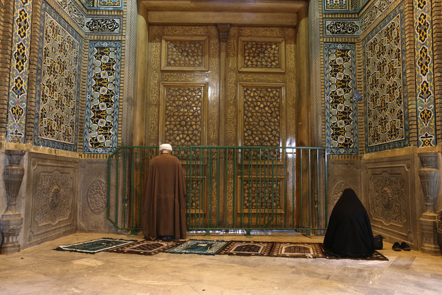 A cleric and a woman pray behind a closed door of Masoume shrine in the city of Qom, some 80 miles (125 kilometers) south of the capital Tehran, Iran, Monday, March 16, 2020. On Monday, Iran closed the Masoume shrine, a major pilgrimage site in the city of Qom, the epicenter of the country's new coronavirus outbreak. Authorities were already restricting access and barring pilgrims from kissing or touching the shrine, but it had remained open. (Photo by AP Photo)