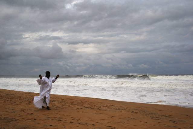 A member of the Church of Aladura prays on the beach on August 20, 2014 in Monrovia, Liberia. He and other church members were praying for God to rescue Liberia from its current crisis. The Ebola virus has killed more than 1,200 people in four African nations, with more in Liberia than any other country. (Photo by John Moore/Getty Images)
