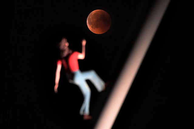 "A ""blood moon"" eclipse is pictured with a sculpture by the American artist Jonathan Borofsky ""Woman walking to the sky"" on July 27, 2018 in Strasbourg, eastern France. The celestial show is the result of the sun, Earth, and Moon lining up perfectly for a lunar eclipse just as the Moon is near its closest orbit point to Earth, making it appear ""super"" large. (Photo by Frederick Florin/AFP Photo)"