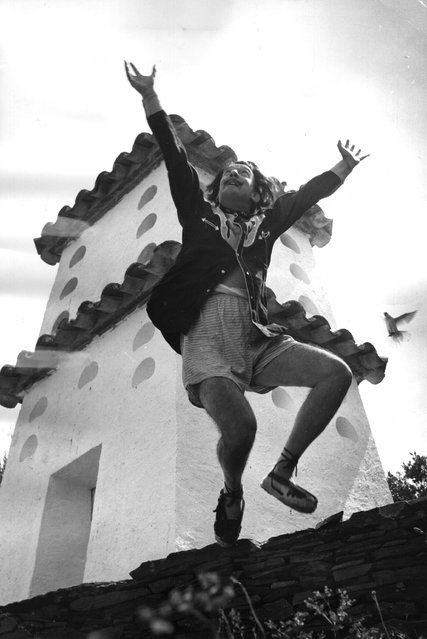Spanish surrealist artist Salvador Dali (1904–1989) cavorting on a rooftop at his home in Cadaques on the Spanish Costa Brava, 1955.   (Photo by Charles Hewitt)