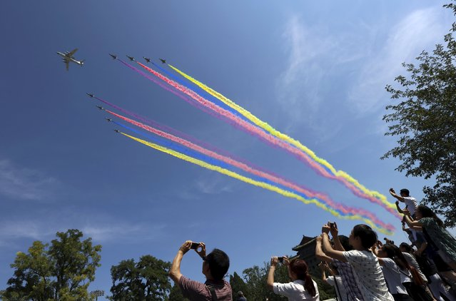 People take pictures as a formation of military airplanes, consisting of one KJ-2000 aircraft and eight J-10 fighter jets, flies across the sky during the military parade marking the 70th anniversary of the end of World War Two, in Beijing, China, September 3, 2015. (Photo by Reuters/Stringer)