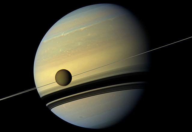 A giant of a moon appears before a giant of a planet undergoing seasonal changes in this natural color view of Titan and Saturn from NASA's Cassini spacecraft, on May 6, 2012. As the seasons have changed in the Saturnian system, and spring has come to the north and autumn to the south, the azure blue in the northern Saturnian hemisphere that greeted Cassini upon its arrival in 2004 is now fading. The southern hemisphere, in its approach to winter, is taking on a bluish hue. This change is likely due to the reduced intensity of ultraviolet light and the haze it produces in the hemisphere approaching winter, and the increasing intensity of ultraviolet light and haze production in the hemisphere approaching summer. (Photo by NASA/JPL-Caltech/SSI)