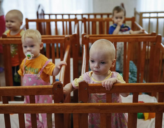 Children who were transferred from orphanages in Donetsk and Makeyevka stand in their cribs in an orphanage in Kramatorsk August 30, 2014. 76 children from orphanages in Donetsk and Makeyevka in eastern Ukraine were sent to Kramatorsk due to fighting between the Ukrainian army and pro-Russian separatists. (Photo by Gleb Garanich/Reuters)