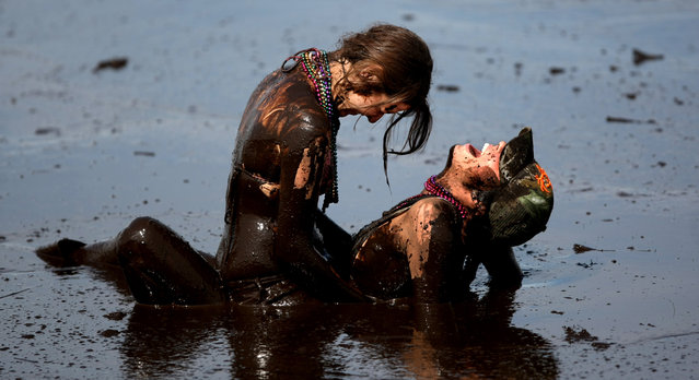 Evans, left, and Welch wrestle in the mud bog. (Photo by Gary Coronado/The Palm Beach Post)