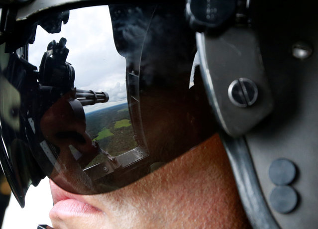 A Colombian anti-narcotics policeman prepares to disembark a helicopter in a rural area of of Calamar in Guaviare state, Colombia, August 2, 2016. (Photo by John Vizcaino/Reuters)