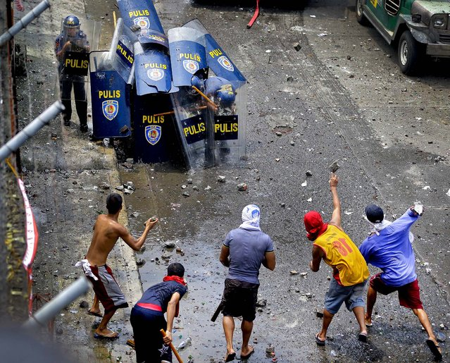 Residents battle with police during a demolition of their shanties at the financial district of Makati City, east of Manila, Philippines, on September 24, 2012.  Police used tear gas and water cannons to disperse the residents protesting  the removal of  more than 200 families  (Photo by Bullit Marquez/Associated Press)