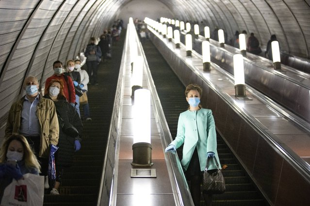 People wearing face masks and gloves to protect against coronavirus, observe social distancing guidelines as they go down the subway on the escalator in Moscow, Russia, Tuesday, May 12, 2020. From Tuesday onward, wearing face masks and latex gloves is mandatory for people using Moscow's public transport. President Vladimir Putin on Monday declared an end to a partial economic shutdown across Russia due to the coronavirus pandemic, but he said that many restrictions will remain in place. (Photo by Alexander Zemlianichenko/AP Photo)
