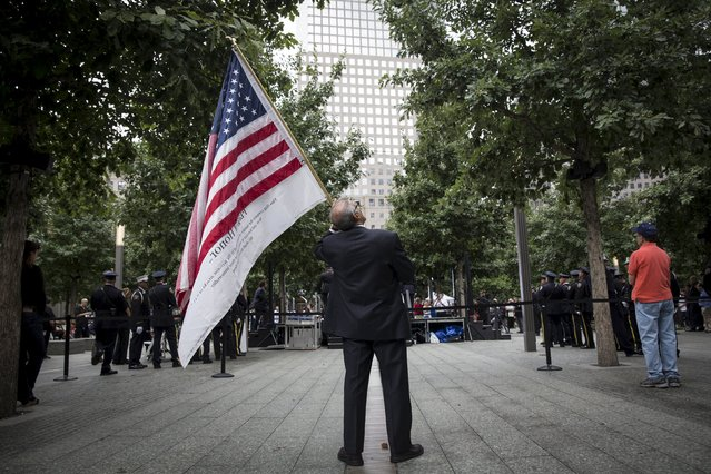A man stands with a U.S. flag during a ceremony marking the 14th anniversary of the attacks on the World Trade Center at The National September 11 Memorial and Museum in Lower Manhattan in New York, September 11, 2015. (Photo by Andrew Kelly/Reuters)