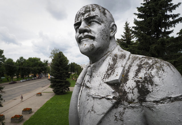"His party's power is long gone, his ideas mostly discredited – but Vladimir Lenin's visage remains a fixture in much of the former Soviet Union. The thousands of statues of him spread across the vast region bring to mind poet Vladimir Mayakovsky's ringing line of devotion: ""Lenin lived, Lenin lives, Lenin will live"". The past tense applies to many of the statues. They were torn down and pulverized by angry mobs, as happened in Kiev during the wave of protests in 2013-14, or methodically demounted by local authorities. Some of the Lenin statues taken down with care were moved from public squares and prominent points to quiet, secluded parks. There Lenin seems less like a fiery leader than a grumpy retiree, his arm outstretched as if trying to call back a bus that sped past him. But in other spots, that arm is clearly calling the masses to rise up and go forward. Viewed as a whole, the statues are monotonous – Lenin is always portrayed as stern – but there are individual nuances. In some, he holds a lapel in a gesture of self-confidence. In others, like the one in the center of Moscow's noisy, traffic-choked Kaluzhskaya Square, he has one hand in his pocket, casually surveying the scene with a boulevardier's air. Of all the statues, the one that may distill the cult of Lenin to its purest form is the seven-meter (25-foot) tall head that dominates the central square of Ulan-Ude, a city 100 kilometers (about 60 miles) southeast of Lake Baikal in southeast Russia. There's no body language to read, just Lenin's judgmental stare. The square was redesigned especially to accommodate the giant head. Removing it would leave the square seeming barren and pointless. There, at least, it's likely that Lenin will live. Here: In this photo taken on August 4, 2017, a statue of Vladimir Lenin stands in the town of Uglich, 200 kilometers (124 miles) north-east of Moscow, Russia. (Photo by Dmitri Lovetsky/AP Photo)"