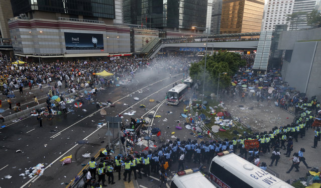 Protesters disperse as riot police fire teargas after thousands of protesters blocked the main street to the financial Central district outside the government headquarters in Hong Kong September 28, 2014. (Photo by Bobby Yip/Reuters)