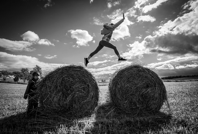 """Hey Kids"". I was traveling by car across beautiful Masurian Lakes district in Poland together with my family. Being impressed with the beauty of the landscape we decided to make a stop by the field of bales and take some nature shots. Before I knew, my niece who trains in gymnastic, was happily jumping from one bale to another presenting her skills. Photo location: Poland. (Photo and caption by Malgorzata Walkowska/National Geographic Photo Contest)"