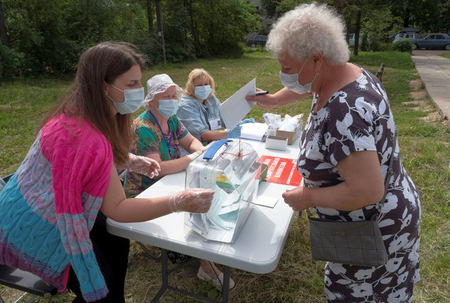 Members of the election commission wearing face masks to protect against coronavirus infection help to a voter to cast her ballot at an outdoor polling station in Naziya village, 80 km (50 miles) east of St.Petersburg, Russia, Sunday, June 28, 2020. Polls have opened in Russia for a week-long vote on a constitutional reform that may allow President Vladimir Putin to stay in power until 2036. (Photo by Dmitri Lovetsky/AP Photo)
