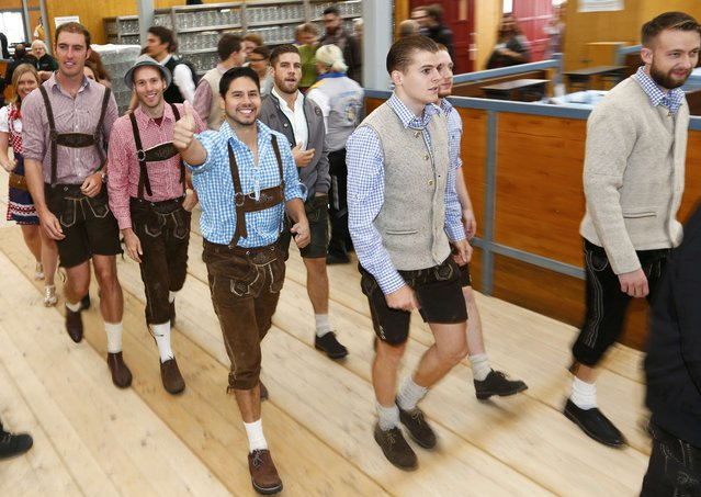 Visitors dressed in traditional Bavarian outfits enter a tent after the opening of the 182nd Oktoberfest in Munich, Germany, September 19, 2015. (Photo by Michaela Rehle/Reuters)