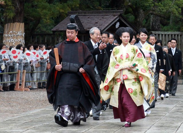 Japans Princess Noriko (R), second daughter of the late Prince Takamado dressed in an ancient Japanese formal court and Kunimaro Senge (L), the eldest son of the chief priest of the Izumo grand shrine walk with their family members for wedding procession at the Izumo grand shrine in Izumo city in Shimane prefecture, western Japan on October 5, 2014. The 26-year-old princess and the 41-year-old Shinto priest held a wedding ceremony at the shrine, where the Senge family has been in charge of rituals. (Photo by AFP Photo/Jiji Press)