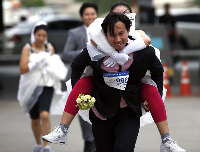 """Thai groom-to-be Nutthawut Nakajun carries his bride-to-be Jirawan Kirdsang as they compete in the """"Running of the Brides"""" event in Bangkok, Thailand, 02 December 2017. (Photo by Rungroj Yongrit/EPA/EFE/Rex Features/Shutterstock)"""