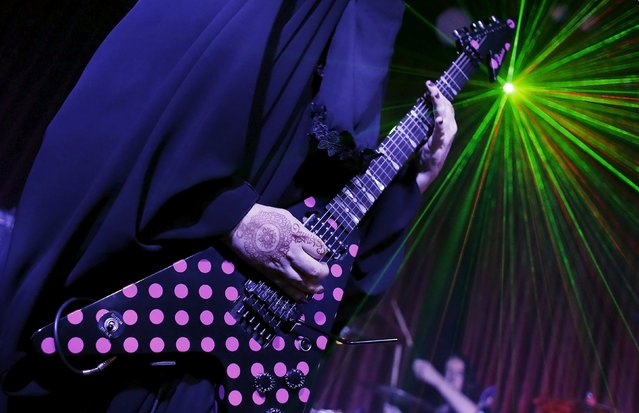 Gisele Marie, a Muslim woman and professional heavy metal musician, plays her Gibson Flying V electric guitar during a concert in Sao Paulo December 16, 2014. (Photo by Nacho Doce/Reuters)
