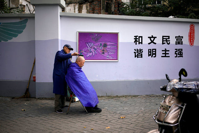 A resident gets a haircut by the roadside in Shanghai, China November 27, 2017. (Photo by Aly Song/Reuters)