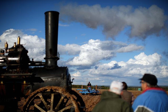 """A ploughman demonstrates with a cultivator or """"Scuffle"""" (R) drawn by a 1917 Fowler AA7 Steam Plough engine on day one of the 2014 """"British National Ploughing Championships"""" on October 11, 2014 in Basingstoke, England. Over 200 ploughmen and women from across the country compete over two days in a range of classes on the 200 acre site in Hampshire. (Photo by Dan Kitwood/Getty Images)"""
